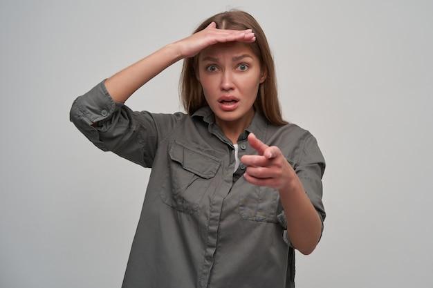 若い女性、茶色の長い髪のきれいな女性。灰色のシャツを着て、額に手をかざし、あなたを指さします。灰色の背景に分離されたカメラで心配そうな顔で見ています
