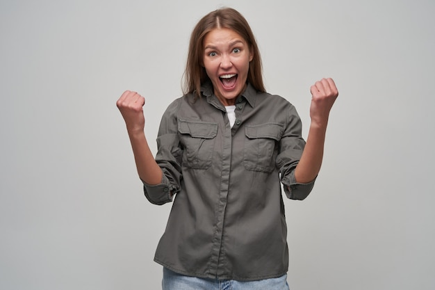 若い女性、茶色の長い髪のきれいな女性。灰色のシャツとジーンズを着て拳を持ち上げ、成功に満足し、興奮した。灰色の背景の上に分離されたカメラで見て