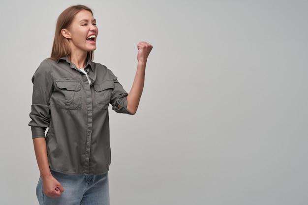 Signora giovane, bella donna con i capelli lunghi castani. indossa una camicia grigia e jeans. tieni il pugno alzato, girato e guarda a destra nello spazio della copia, mostrando la sua eccitazione, isolato su sfondo grigio