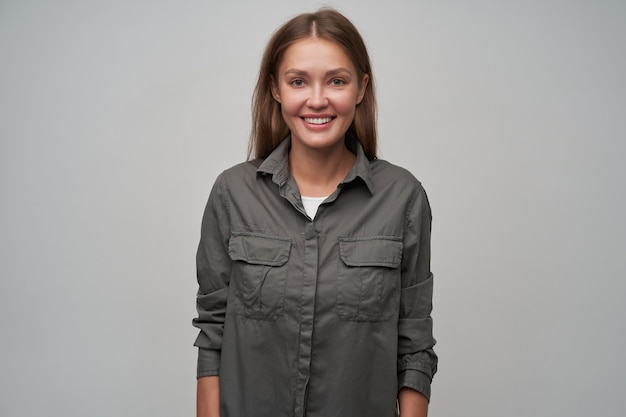 Young lady, pretty woman with brown long hair. wearing grey shirt and smiling. introducing her self. confident posture. watching at the camera isolated over grey background