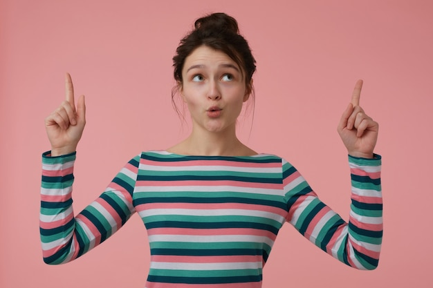 젊은 아가씨, 갈색 머리와 롤빵 예쁜 여자. 스트라이프 블라우스를 입고 관심을 보이며 놀랐습니다. 감정적 인 개념. 파스텔 핑크 벽 위에 절연 복사 공간에서 가리키는