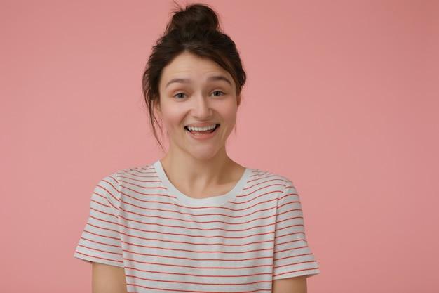 若い女性、ブルネットの髪とパンを持つきれいな女性。赤い帯のtシャツを着て、幸せに笑っています。感情的な概念。パステルピンクの壁に分離