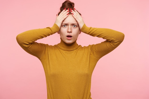 Young lady, pretty woman with ginger hair, freckles and bun. wearing gold turtleneck sweater and touching her head with hands, terrified. isolated over pastel pink wall