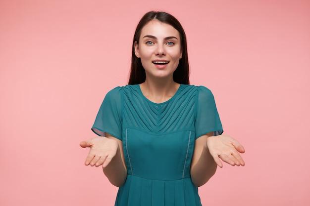 젊은 아가씨, 긴 갈색 머리를 가진 예쁜 여자. 웃 고 손바닥으로 그녀의 손을 잡고보고, 파스텔 핑크 벽 위에 절연 공간을 복사합니다. 에메랄드 드레스를 입고