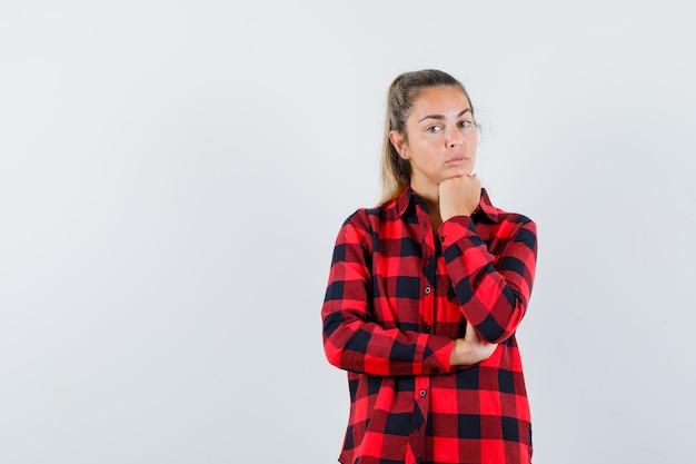 Giovane donna appoggiando il mento sul pugno in camicia a quadri e guardando pensieroso