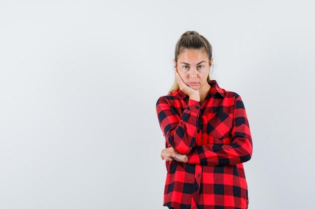 Giovane donna appoggiando il mento a portata di mano in camicia controllata e guardando pensieroso