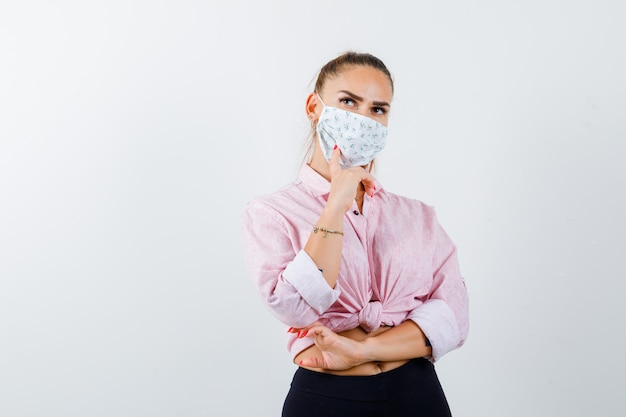 Young lady propping chin on hand in shirt, mask and looking pensive. front view.