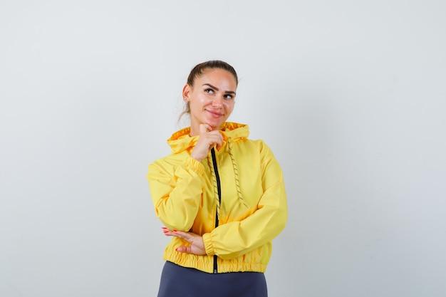 Giovane signora che puntella il mento a portata di mano in giacca gialla e sembra pacifica. vista frontale.
