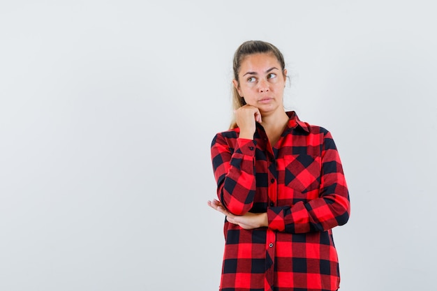 チェックシャツを着て拳で顎を支え、思慮深く見える若い女性