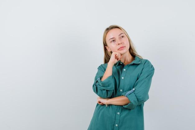 緑のシャツを着て拳で顎を支え、物思いにふける若い女性