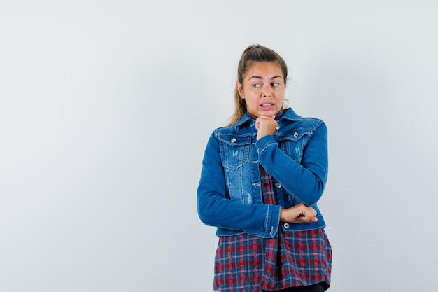 シャツ、ジャケット、心配そうに見える、正面図で拳で顎を支えている若い女性。