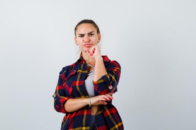 上に拳で顎を支え、格子縞のシャツと真剣に見える若い女性。正面図。