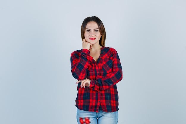 チェックシャツを着て手であごを支え、陽気に見える若い女性、正面図。