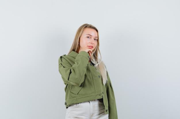 Юная леди подпирает подбородок рукой в куртке, штанах и выглядит деликатно, вид спереди.