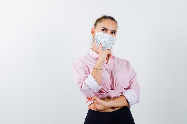 シャツ、マスク、物思いにふけるように手で顎を支えている若い女性。正面図。