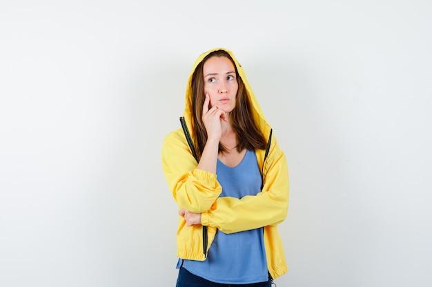 Tシャツ、ジャケットで手に顎を支え、物思いにふける若い女性
