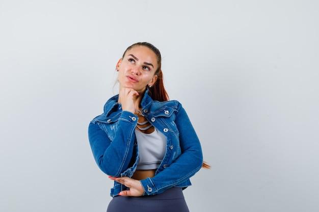 Юная леди подпирает рукой подбородок в топе, джинсовой куртке и задумчиво выглядит. передний план.