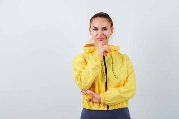 Молодой леди подпирая подбородок рукой в желтой куртке и выглядит уверенно, вид спереди.