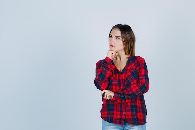 手で顎を支え、チェックのシャツで目をそらし、物思いにふける、正面図を見て若い女性。