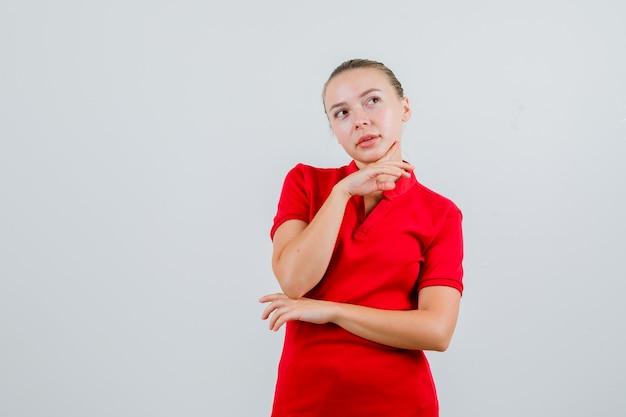 赤いtシャツのあごに指を支え、希望に満ちた若い女性