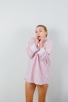 ピンクのシャツの襟を引っ張って、かわいく見える若い女性