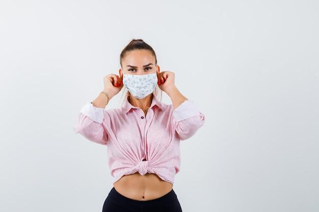 Giovane donna che tira giù i lobi delle orecchie in camicia, maschera e sembra divertente, vista frontale.