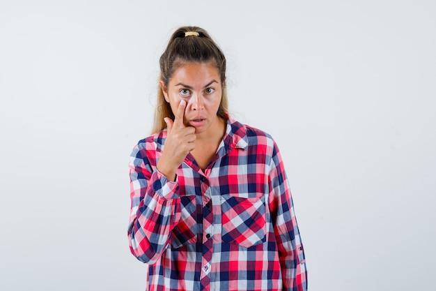 Giovane donna che abbassa la palpebra in camicia a quadri e sembra perplessa. vista frontale.
