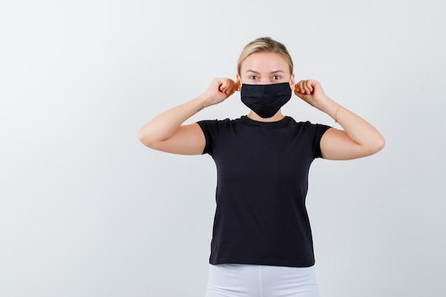 Giovane donna che tira i lobi delle orecchie con le dita in maglietta, pantaloni, maschera medica e sembra divertente