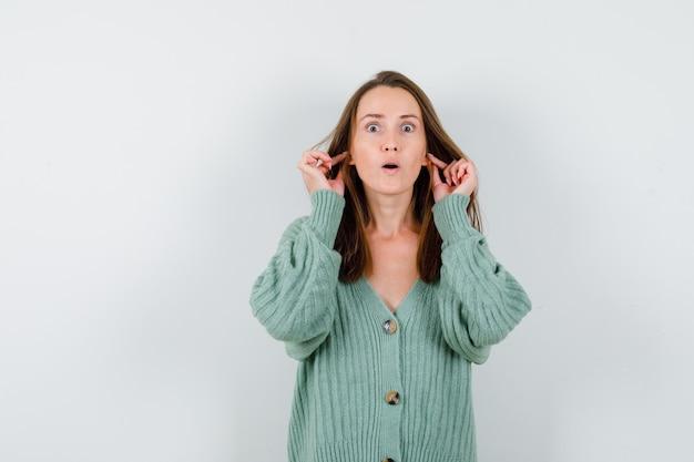 ウールのカーディガンで指で耳を引っ張ってショックを受けている若い女性。正面図。