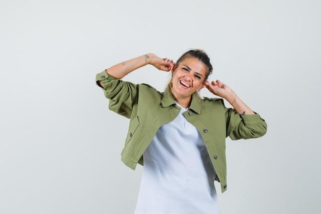 Девушка в куртке с футболкой тянет за уши и выглядит удивленно