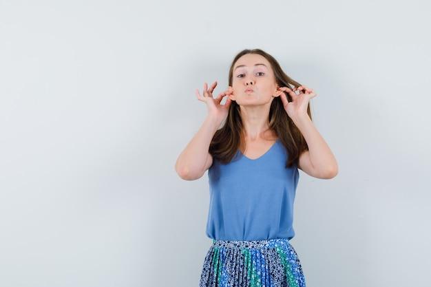 Девушка тянет за уши, надувает губы в майке, юбке и выглядит смешно