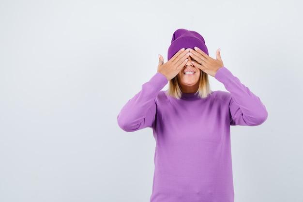 Giovane donna in maglione viola, berretto che copre gli occhi con le mani e sembra gioiosa, vista frontale.