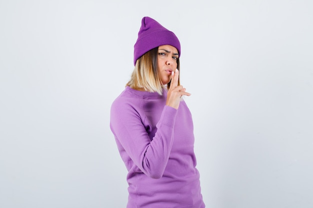 Young lady in purple sweater, beanie showing gun gesture and looking confident , front view.