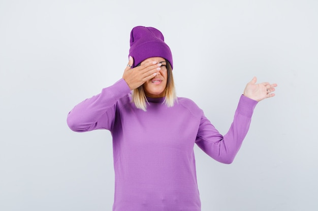 Giovane donna in maglione viola, berretto con la mano sugli occhi mentre mostra qualcosa e sembra allegra, vista frontale.