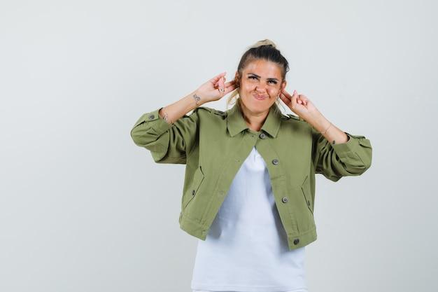 Tシャツのジャケットに耳を押して、おかしな顔をしている若い女性