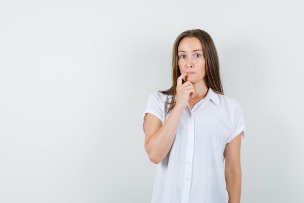 白いブラウスで彼女の口に指を置き、思慮深く見える若い女性