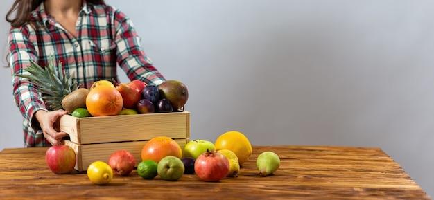테이블에 과일 나무 상자를 넣어 젊은 아가씨