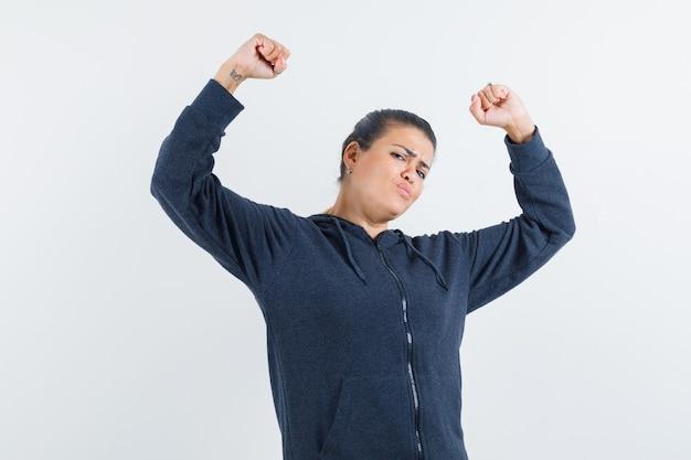 재킷에 우승자 제스처를 보여주는 팔을 제기하고 유연하게 보이는 젊은 아가씨. 전면보기.