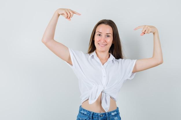 Giovane donna che alza le braccia mentre si indica in camicetta bianca e sembra felice. vista frontale.