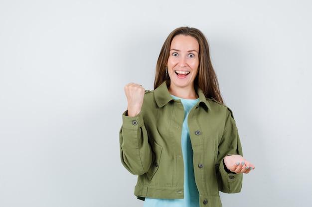 티셔츠, 재킷에 주먹을 꽉 쥐고 행복해 보이는 젊은 여성. 전면보기.