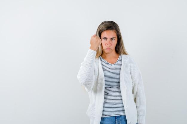 Tシャツ、ジャケットでくいしばられた握りこぶしを上げて、意地悪に見える若い女性、正面図。