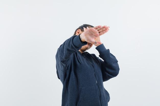 Giovane donna alzando la mano per nascondersi dalle riprese della fotocamera in giacca