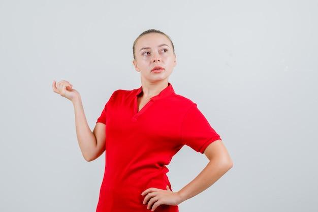 赤いtシャツで目をそらし、物思いにふける見ながら手を上げる若い女性