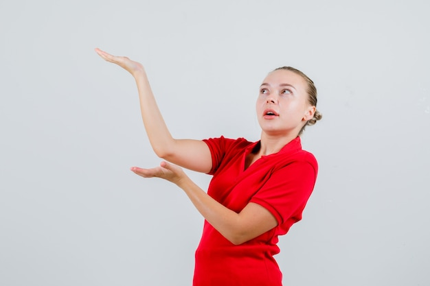Young lady raising hands as holding something in red t-shirt