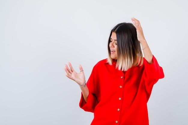 Молодая дама поднимает руки в сторону в красной рубашке oversize и выглядит радостной, вид спереди.