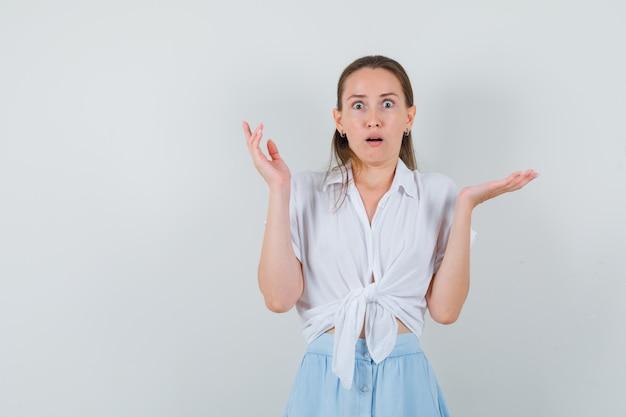 Giovane donna che alza le mani in camicetta e gonna e sembra confusa