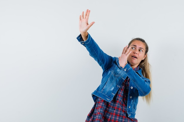 Young lady raising hands to defend herself in shirt, jacket and looking scared. front view.
