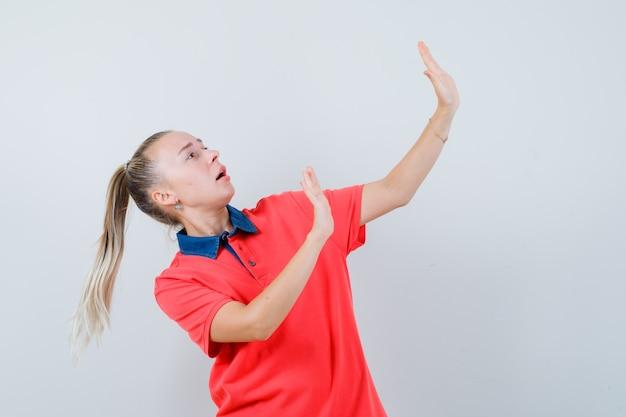 젊은 아가씨 t- 셔츠에 예방 방식으로 손을 올리고 두려워보고