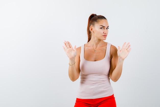 Giovane donna che alza le mani in gesto di resa in canottiera beige e sembra cupa