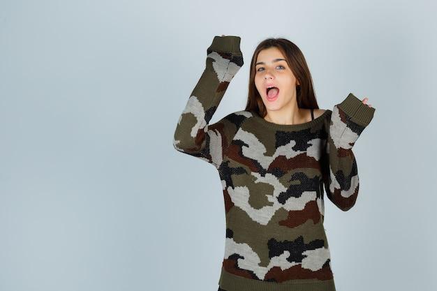 Giovane signora che alza le mani in gesto di resa in maglione e guardando divertito
